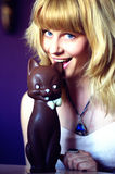 Young pretty woman tasting chocolate cat. Young pretty woman tasting belgian milk chocolate figure of a cat with white bow Royalty Free Stock Image