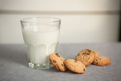 Milk with chocolate chip cookies on gray table. Simple breakfast on the kitchen Royalty Free Stock Image