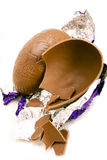 Milk chocolate easter egg. A halved and broken Easter egg with wrapper over white Stock Photos