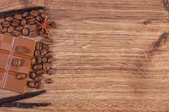 Milk chocolate, fragrant vanilla sticks and coffee grains, copy space for text Royalty Free Stock Photos