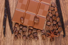 Milk chocolate, fragrant vanilla sticks and coffee grains Royalty Free Stock Photos