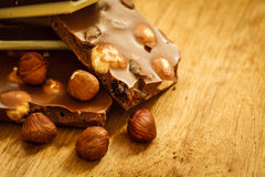 Milk chocolate and hazelnuts on wooden table Royalty Free Stock Photography