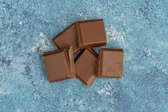 Milk chocolate pieces  on background from top view stock image