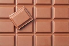Milk Chocolate. Slice of milk chocolate put on a chocolate block Stock Images