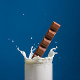 Milk and chocolate. Splash of milk, caused by falling into a chocolate . Isolated on a blue background Stock Image