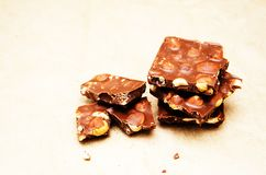 Milk chocolate with whole hazelnut on paper background royalty free stock photos