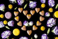Milk chocolates heart surrounded with flowers from above on black Royalty Free Stock Photos