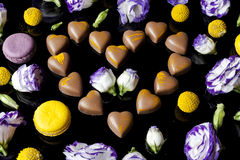 Milk chocolates heart surrounded with flowers from side on black Royalty Free Stock Photos
