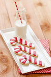 Milk and Christmas cookies. Three Christmas candy cane sugar cookies rest on a white rectangle platter next to a small farm bottle of milk with a red and white royalty free stock images