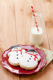 Milk and Christmas cookies. Two snowmen sugar cookies rest on red plate next to a small farm bottle of milk with a red and white striped straw Royalty Free Stock Photos