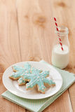 Milk and Christmas cookies. Two blue snowflake sugar cookies rest on white plate next to a small farm bottle of milk with a red and white striped straw Royalty Free Stock Photos