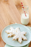 Milk and Christmas cookies. Two white snowflake sugar cookies rest on blue plate next to a small farm bottle of milk with a red and white striped straw Royalty Free Stock Photos