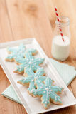 Milk and Christmas cookies. A row of blue snowflake sugar cookies rest on a white tray next to a small farm bottle of milk with a red and white striped straw Royalty Free Stock Photo
