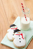 Milk and Christmas cookies. Two snowmen sugar cookies rest on blue napkin next to a small farm bottle of milk with a red and white striped straw Stock Photography