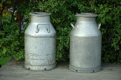 Milk churn. Two milk churns on a bench in Sweden Stock Image