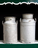 Milk churns. Two milk churns with black background stock images