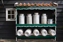 Milk churns. Several milk churns on shelves royalty free stock photo
