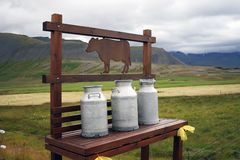 Milk churns. Three milkchurns waiting on a wooden bench to get collected in a rural landscape Stock Image