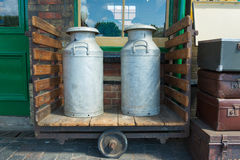 Milk churns on wooden trolley Royalty Free Stock Photo