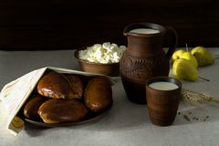 Milk, cottage cheese, pies in earthenware, pears. Milk in a clay jug, cottage cheese and homemade fresh patties on a clay plate, freshly harvested pears Stock Image
