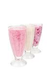 Milk cocktail with banana, blackcurrant and raspberry in a glass isolated on white Royalty Free Stock Image