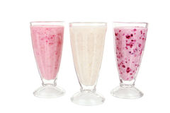 Milk cocktail with banana, blackcurrant and raspberry in a glass isolated on white. Stock Image