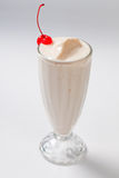 Milk cocktail with a cherry in a tall glass Royalty Free Stock Photo