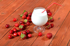 Milk cocktail on wooden old table, juicy berries. Stock Photos