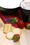 Milk and coffee with biscuits and strawberries. Cup of cappuccino and black cup with strawberries and cookies on pine wood Royalty Free Stock Photos