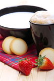 Milk and coffee with biscuits and strawberries. Cup of cappuccino and black cup with strawberries and cookies on pine wood Stock Images
