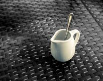 Milk Coffee Cup. White classy milk  coffee cup with silver spoon inside on black table Stock Photography
