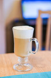 Milk coffee. With foam in a glass mug on wooden table Royalty Free Stock Photos