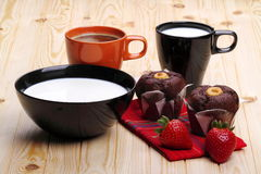 Milk, coffee, muffins of chocolate and strawberries. Cup of coffee and cup of milk with a cup full of milk and strawberries on pine wood Royalty Free Stock Photography