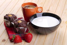 Milk, coffee, muffins of chocolate and strawberries. Cup of milk and cup of coffee with sweets on a pine wood plan Royalty Free Stock Images