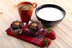Milk, coffee, muffins of chocolate and strawberries. Cup of milk and cup of coffee with sweets on a pine wood plan Royalty Free Stock Image