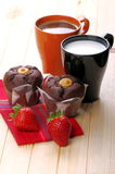 Milk and coffee with muffins. Cup of milk and cup of coffee with chocolate muffins and strawberries on pine wood Royalty Free Stock Image