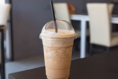 Milk coffee smoothie in plastic cup. Cappuccino frappe in plastic cup. Take away package. Easy cup. Refreshment drink. On white table stock photos