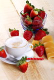 Milk and coffee and strawberries. Cappuccino with cup full of strawberries and afternoon snack on wood of fir Royalty Free Stock Photo