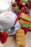 Milk and coffee and strawberries. Cappuccino cup full of strawberries and afternoon snack on wood of fir Royalty Free Stock Photography