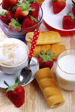 Milk and coffee and strawberries. Cappuccino cup full of strawberries and afternoon snack on wood of fir Royalty Free Stock Image