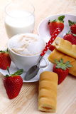 Milk and coffee and strawberries. Coffee with milk and strawberries with a snack of fir wood Stock Images