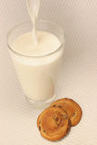 Milk and cookies. Pouring a glass of milk and cookies Stock Photography