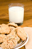 Milk and Cookies. Oatmeal Chocolate Chip cookies and milk with napkin on oak table Royalty Free Stock Photography