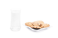Milk and cookies. Close-up shot of cookies on a platter with a glass of milk  on white background Royalty Free Stock Photography
