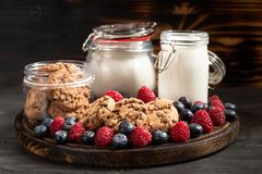 Milk, cookies, flour recipients and forest fruits placed on rounded wooden platter royalty free stock photos