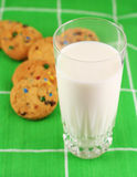 Milk and cookies, focus on milk. Green background Stock Photo