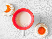 Milk and cookies. Overhead view of a red and white cup filled with frothy milk on a decorative tablecloth with two orange jam filled cookies, one bitten, in a Stock Images