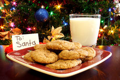 Milk and Cookies for Santa. A plate of cookies and a glass of milk in front of a Christmas tree with a card for Santa Royalty Free Stock Photo