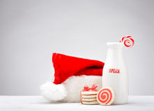 Milk and Cookies for Santa. Milk bottle, pinwheel cookies and a candy cane for Santa over a white background Royalty Free Stock Photos