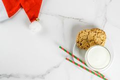 Milk and cookies for Santa Claus. Christmas concept, greeting card. Milk glass and cookies for Santa Claus with Santa`s hat on white marble background, copy Stock Photo